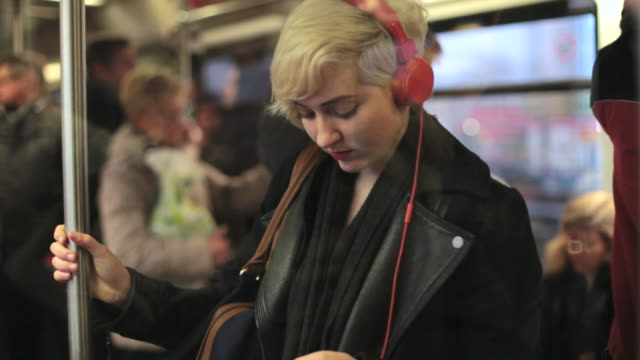 ms ts shot of woman riding commuter train at rush hour / berlin, germany  - headphones stock videos & royalty-free footage