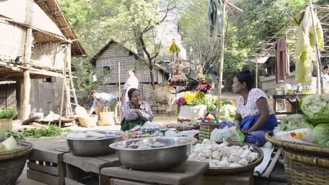 MS Shot of Woman selling food on myinkaba market / Bagan, Mandalay Division, Myanmar