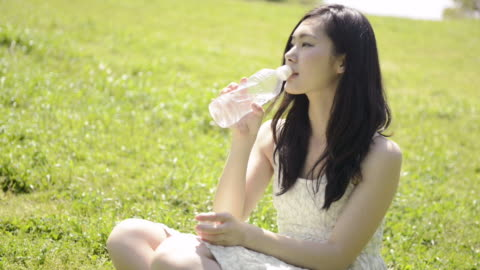 ms shot of woman sits down on lawn and drinks water / uji, kyoto, japan  - dricksvatten bildbanksvideor och videomaterial från bakom kulisserna