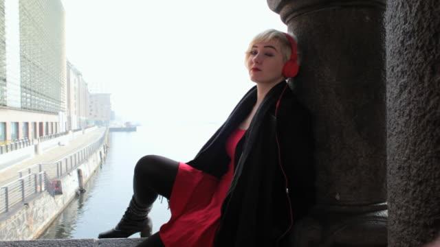 ms ts shot of woman sitting on bridge close to mediaspree listening to music / berlin, germany  - トレンチコート点の映像素材/bロール