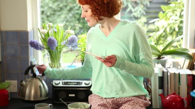 cu td tu shot of woman sitting on kitchen worktop looking at tablet computer while making tea, having breakfast / london, united kingdom - redhead stock videos & royalty-free footage