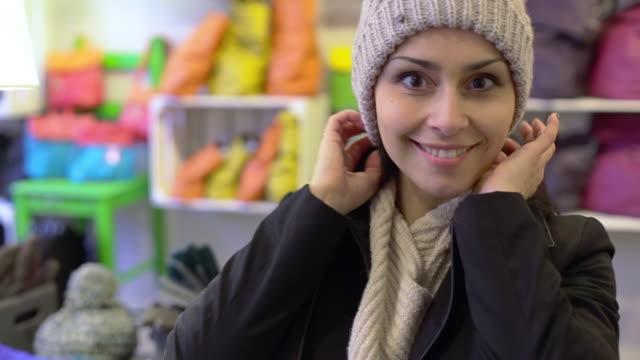 CU TS Shot of Woman smiling, trying on cotton cap inside store / Potsdam, Brandenburg, Germany