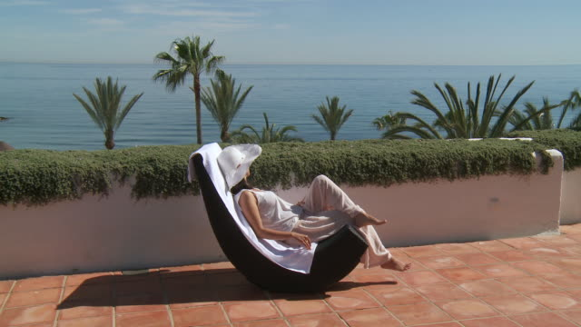 ws shot of woman sunbathing in rocking chair and view of seashore / marbella, andalusia, spain - rocking chair stock videos & royalty-free footage
