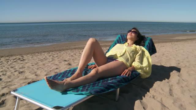 vídeos de stock e filmes b-roll de ms shot of woman sunbathing on beach / marbella, andalusia, spain - apanhar sol
