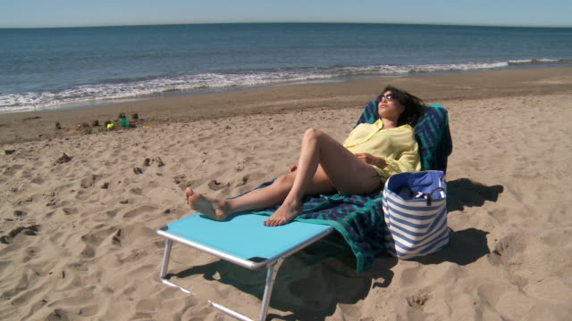 ws shot of woman sunbathing on beach / marbella, andalusia, spain - liegen stock-videos und b-roll-filmmaterial
