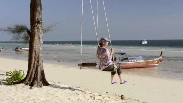 vídeos y material grabado en eventos de stock de ms shot of woman swing on sandy beach / ko hai, krabi, thailand - mar de andamán