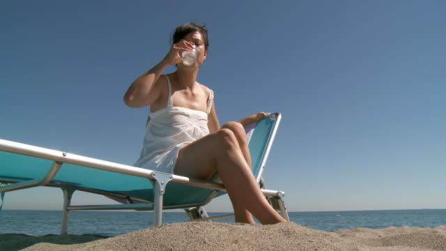 vídeos y material grabado en eventos de stock de ms la shot of woman take fresh glass water on beach / marbella, andalusia, spain - tumbona