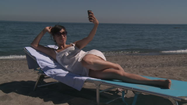 shot of woman take selfie on beach. - auf der seite liegen stock-videos und b-roll-filmmaterial