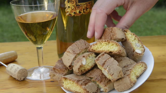 CU Shot of Woman takes piece of cantuccini, Vin Santo / Siena, Tuscany, Italy