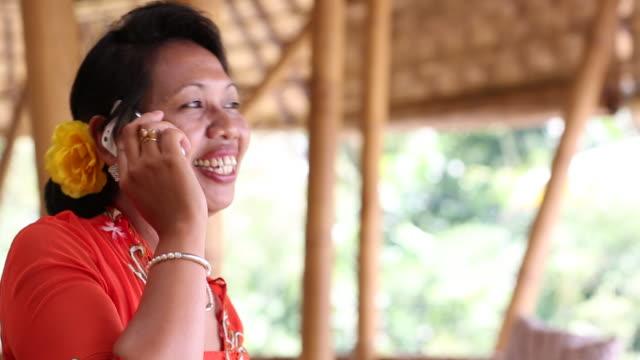 CU PAN Shot of woman talking on her cellphone / Ubud, Bali, Indonesia