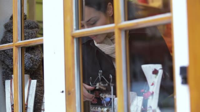 MS TS Shot of Woman tries on earrings inside shop behind window / Potsdam, Brandenburg, Germany