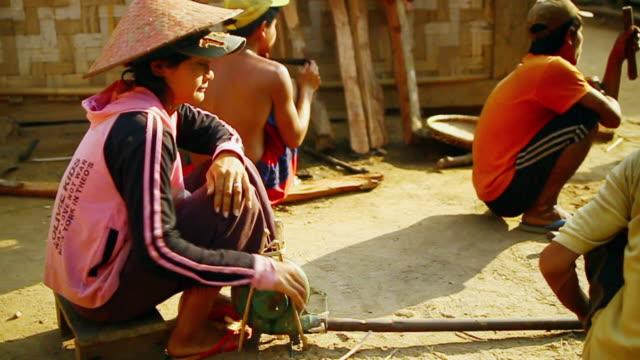 vidéos et rushes de ms slo mo shot of woman turning handle of small engine / muang ngoi, luang prabang, laos - chapeau de paille