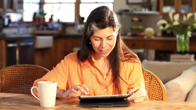 ms shot of woman using tablet and drinking coffee at home / lamy, new mexico, united states - lamy new mexico stock videos and b-roll footage