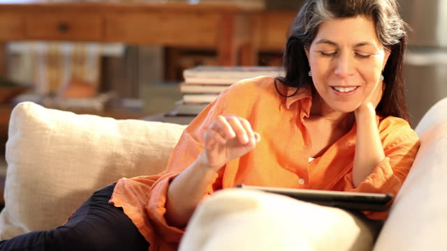 vidéos et rushes de ms tu shot of woman using tablet while relaxing on couch / lamy, new mexico, united states - une seule femme d'âge moyen