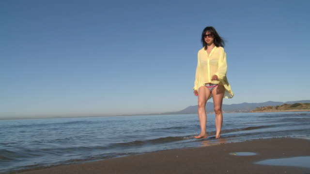 ws shot of woman walking on beach / marbella, andalusia, spain - 中年女子 個影片檔及 b 捲影像