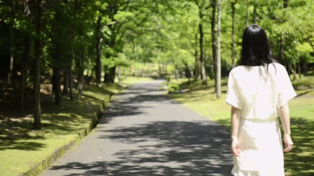 ms shot of woman walks the way of green full park / uji, kyoto, japan  - 後ろ姿点の映像素材/bロール
