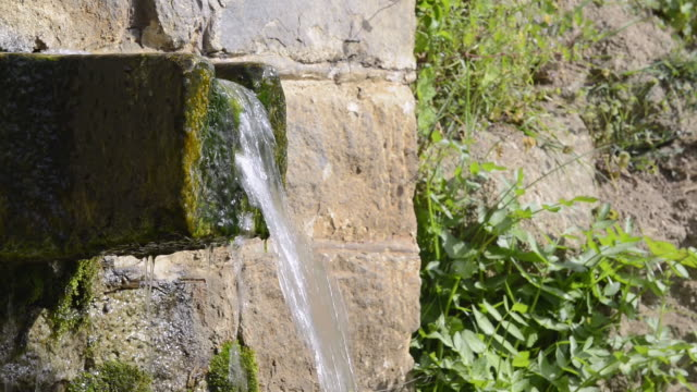 CU Shot of Woman washing hands at old stone fountain / Piana, Corsica, France