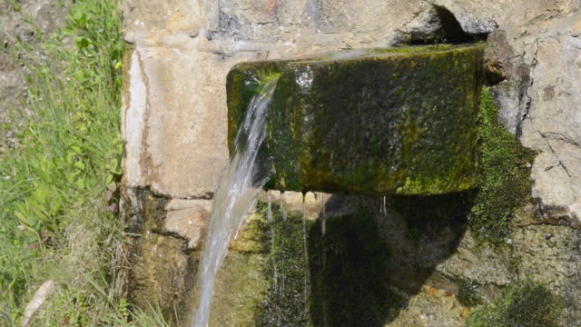 cu shot of woman washing hands at old stone fountain / piana, corsica, france - ピアナ点の映像素材/bロール