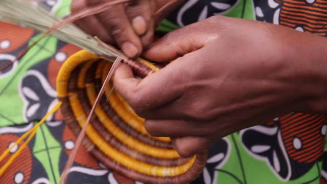 stockvideo's en b-roll-footage met cu shot of woman weaving basket / kigez, kabale, uganda - wiese