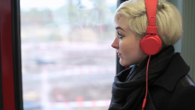 MS TS Shot of woman with red headphones riding train looking out of window / Berlin, Germany
