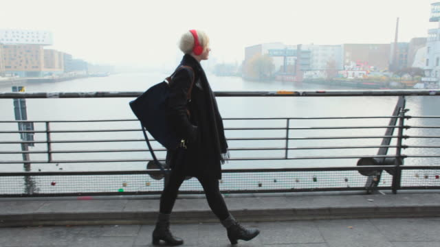 ms ts shot of woman with red headphones walking along bridge across river spree and listening to music / berlin, germany  - ascoltare video stock e b–roll