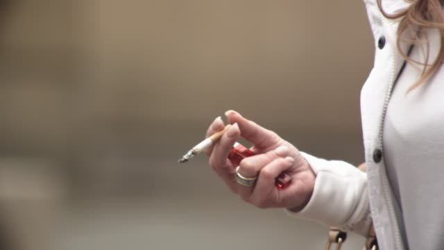 cu ts slo mo shot of woman's cigarette / united kingdom - zigarette stock-videos und b-roll-filmmaterial