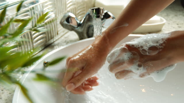 vídeos de stock e filmes b-roll de cu slo mo shot of woman's hands being washed in sink / united kingdom - soap sud