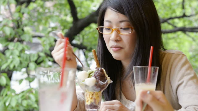 CU Shot of women eating sweets happily in café / Kyoto, Japan