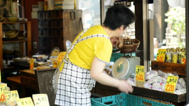 ms pan shot of women greengrocer has weighed in shiitake storefront / toyooka, hyogo, japan - shiitake stock videos & royalty-free footage