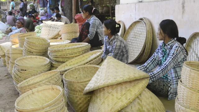 ms shot of women selling straw hats on nyaung u market / bagan, mandalay division, myanmar - korb stock-videos und b-roll-filmmaterial
