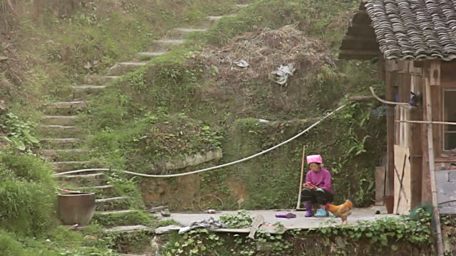 stockvideo's en b-roll-footage met ws shot of women sitting outside of house / yao village, huangluo, china - alleen één mid volwassen vrouw
