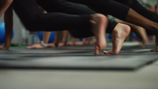 shot of women's feet and legs performing mountain climber exercises on the floor at a gym - pilates stock videos and b-roll footage