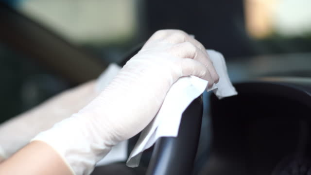 vídeos de stock e filmes b-roll de cu shot of women's hand in glove wiping down steering wheel. - limpo