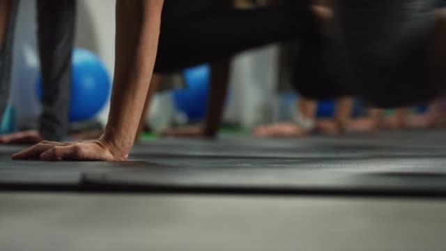 colpo di mani, braccia e gambe delle donne che eseguono esercizi di alpinisti sul pavimento in palestra - pilates video stock e b–roll