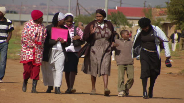 vídeos y material grabado en eventos de stock de ms shot of women's walking on country road with talking with each other / durban south africa - kwazulu natal