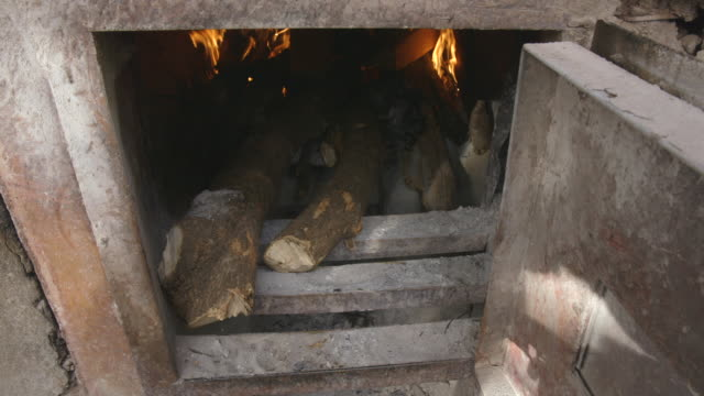 Shot of wood being placed into a furnace at a ylang-ylang distillery.