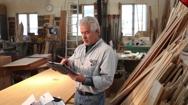 ms shot of woodworker talking on phone in his work station / lamy, new mexico, united states - lamy new mexico stock videos and b-roll footage