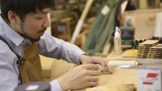 vidéos et rushes de ms shot of woodworker working in his work station / kyoto, japan - un seul homme d'âge moyen