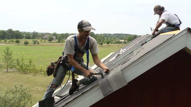 ms shot of worker cutting edge shingle to fit with another worker to right / chelsea, michigan, united states - provincial reconstruction team stock videos & royalty-free footage
