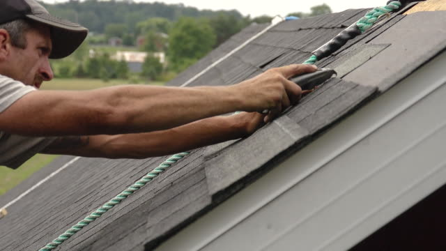 ms shot of worker cutting shingle and hammering / chelsea, michigan, united states - ziegel stock-videos und b-roll-filmmaterial
