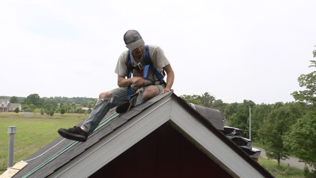 ms shot of worker hammering last shingle at top of roof / chelsea, michigan, united states - rebuilding stock videos & royalty-free footage