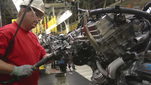 ms shot of worker installing components on an internal combustion engine in an auto assembly plant / princeton, indiana, united states - motore video stock e b–roll
