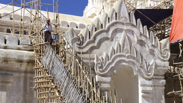MS Shot of Worker on Ananda Pagoda which is scaffolded with bamboo / Bagan, Mandalay Division, Myanmar