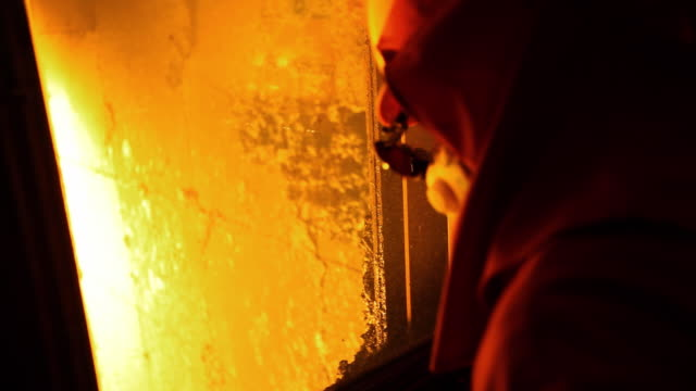 Shot of worker with fire retardant clothing watching blast furnace