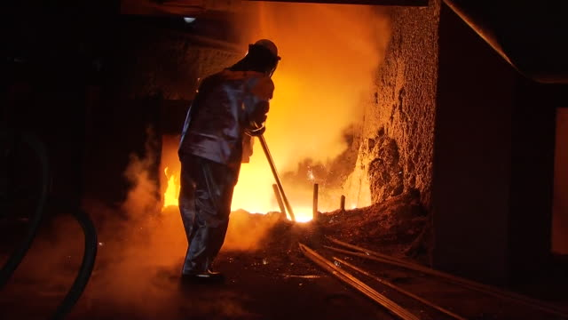 ms zi shot of worker with fire retardant clothing working in furnace / gwangyang, jeollanamdo, south korea - gefahr stock-videos und b-roll-filmmaterial