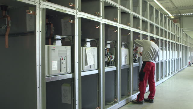 stockvideo's en b-roll-footage met ms pan shot of worker working in voltage distribution switchgear assembly shop at switchgear plant / konz, rhineland palatinate, germany - bord hoogspanning
