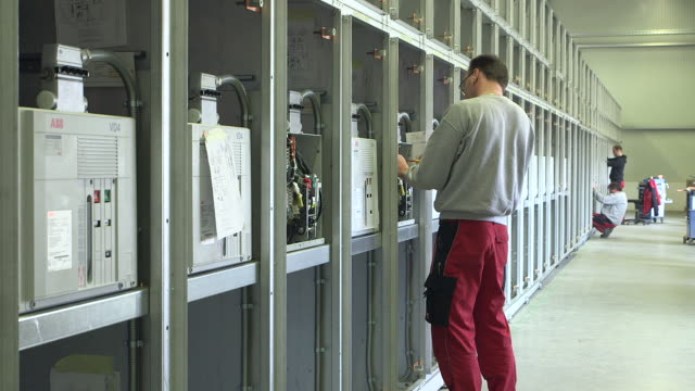 stockvideo's en b-roll-footage met ms shot of worker working in voltage distribution switchgear assembly shop at switchgear plant / konz, rhineland palatinate, germany - bord hoogspanning