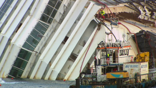 ms shot of workers attach cables to exposed side of costa concordia cruise ship as part of salvage operation / giglio porto, tuscany, italy - 救助隊点の映像素材/bロール