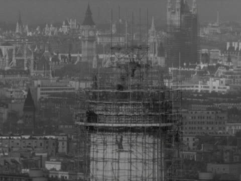 stockvideo's en b-roll-footage met shot of workers building one of the four chimneys of battersea power station big ben and the houses of parliament can be see in the background 1958 - wandsworth