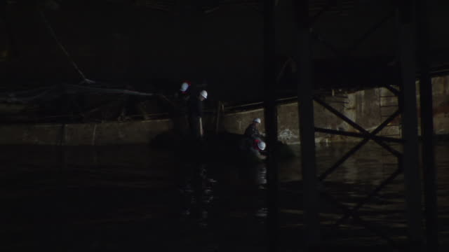 ms shot of workers set up cables on grounded costa concordia cruise ship at night / giglio porto, tuscany, italy - rescue worker stock videos and b-roll footage